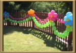 flowers and balloon swags on fence
